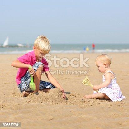 604367022 istock photo Two children playing on sandy beach 503377791