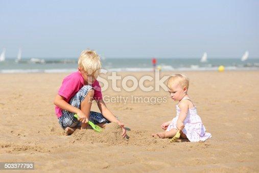 604367022 istock photo Two children playing on sandy beach 503377793