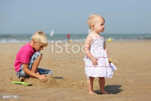 604367022 istock photo Two children playing on sandy beach 503377801