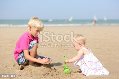 604367022 istock photo Two children playing on sandy beach 503377881