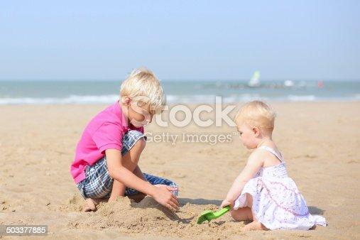 604367022 istock photo Two children playing on sandy beach 503377885