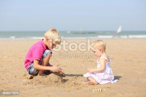 604367022 istock photo Two children playing on sandy beach 503377975