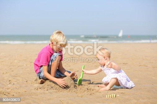 604367022 istock photo Two children playing on sandy beach 503400823