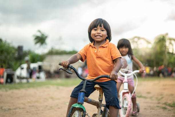 Two Children Riding a Bicycle in a Rural Place Beautiful shooting of how Brazilian Natives lives in Brazil indigenous peoples of the americas stock pictures, royalty-free photos & images