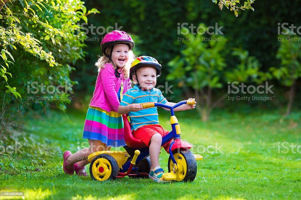 Two children riding bikes stock photo