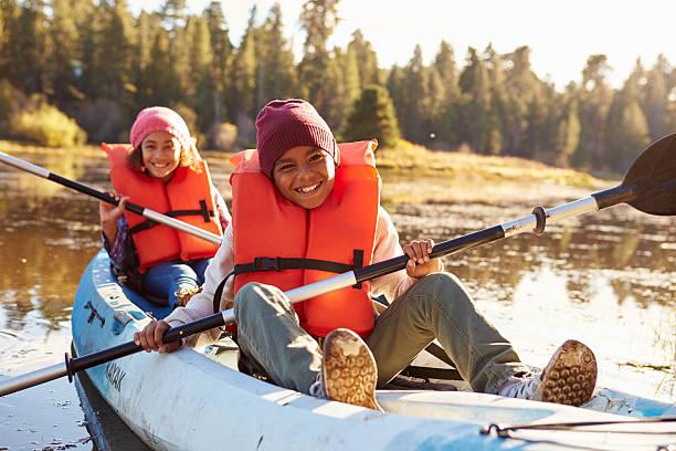 Two Children Rowing Kayak On Lake Two Children Rowing Kayak On Lake canoeing stock pictures, royalty-free photos & images
