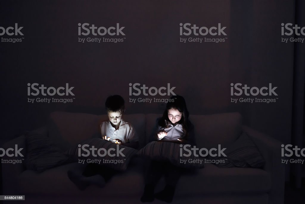 Two children, sitting in a dark, playing with gadgets stock photo