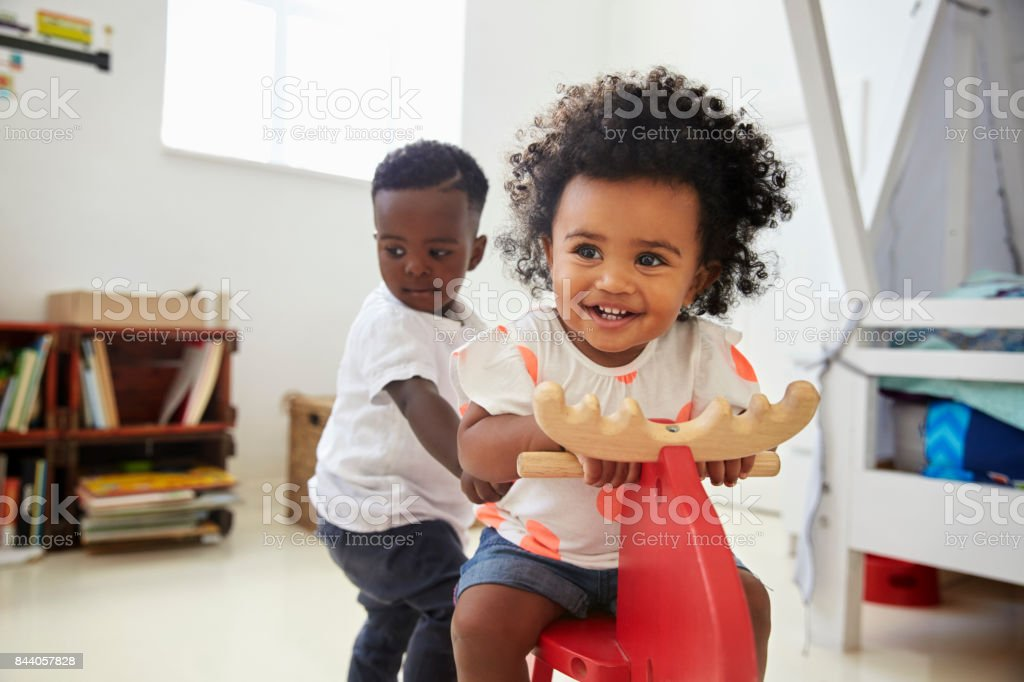 Two Children Sitting On Ride On Toy In Playroom stock photo