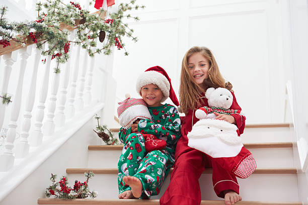 two children sitting on stairs in pajamas at christmas - christmas tree stockfoto's en -beelden