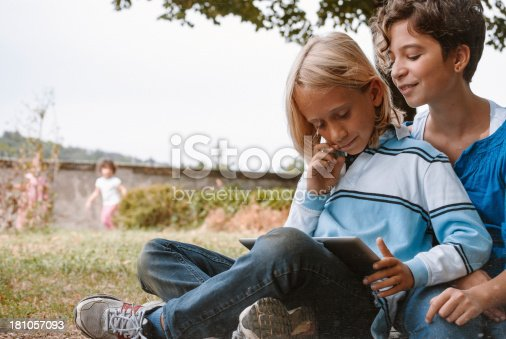 istock Two children using a tablet outdoors 181057093