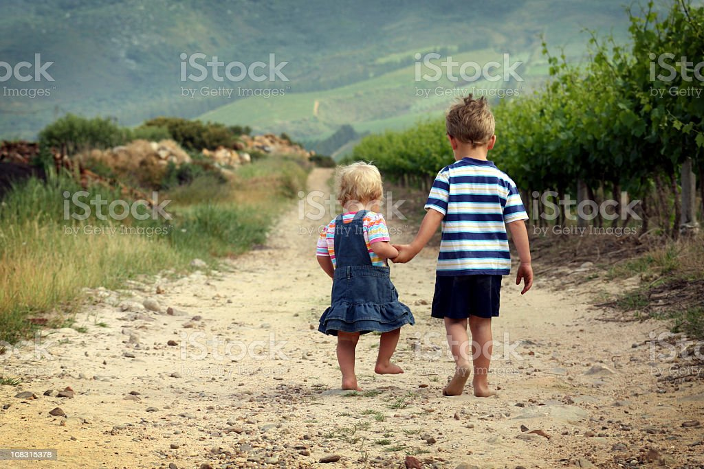 Two children walking away barefoot on sand royalty-free stock photo