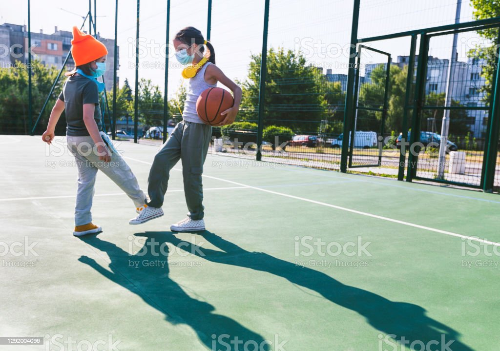 Two children with face protective masks using foot bump. High five without hands Two little children with face protective masks using foot bump on a playground. High five without hands. New style handshakes and greetings. New normal. Covid-19. Child Stock Photo
