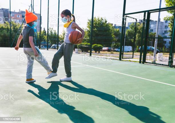 Two Children With Face Protective Masks Using Foot Bump High Five Without Hands Stock Photo - Download Image Now