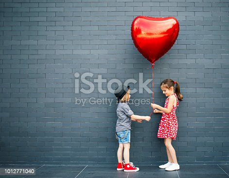 Two children with heart shape air balloon. First date. Love concept.