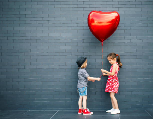 Two children with heart shape air balloon - foto stock