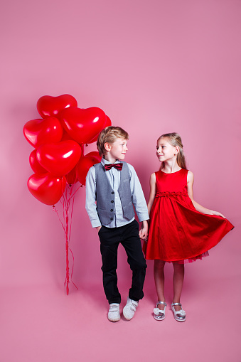 518335358 istock photo Two children with heart shape air balloons on pink background 1199744970