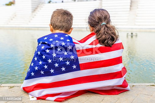 istock Two children wrapped in the American flag 1144553439