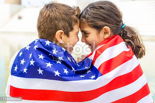 istock Two children wrapped in the American flag 1144553440