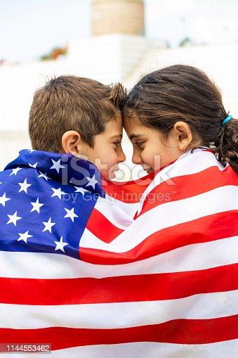 istock Two children wrapped in the American flag 1144553462