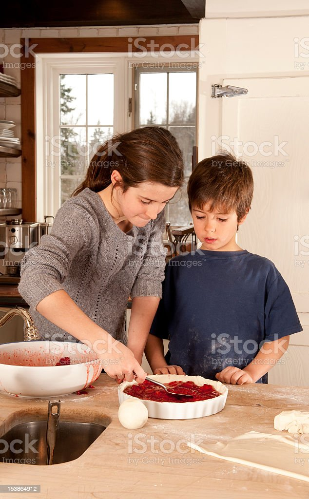 Two childrens cooking strawberries pie royalty-free stock photo
