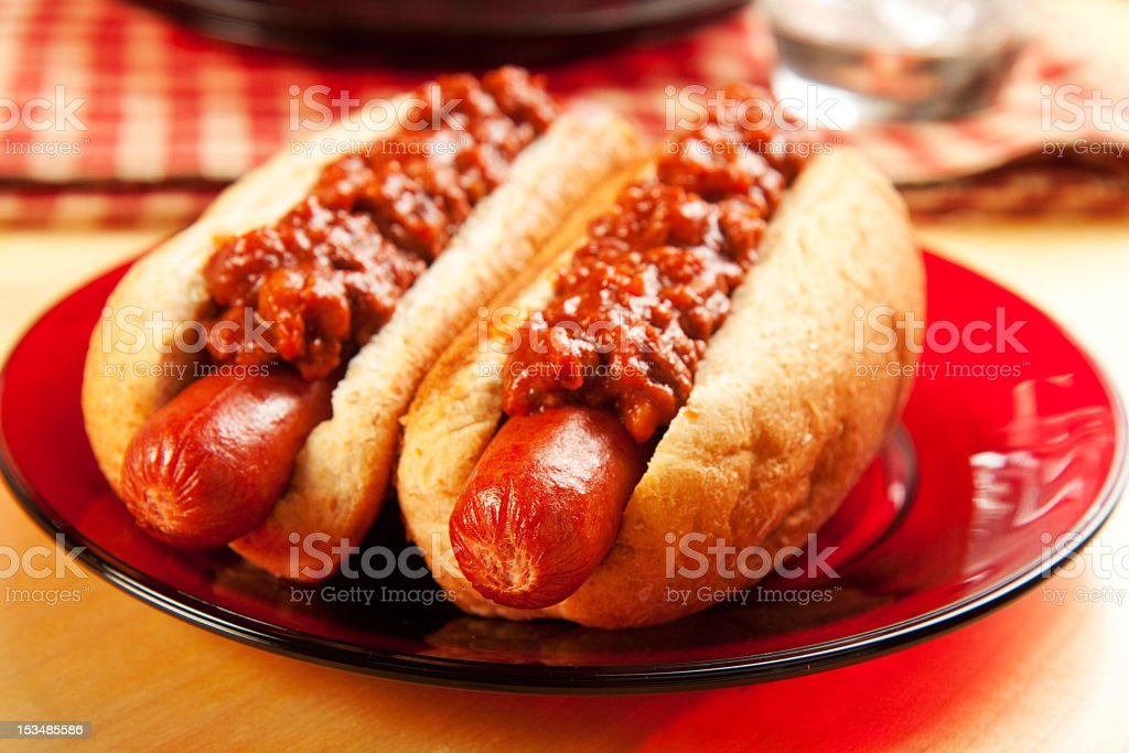 Two chili dogs on a red plate at a picnic stock photo