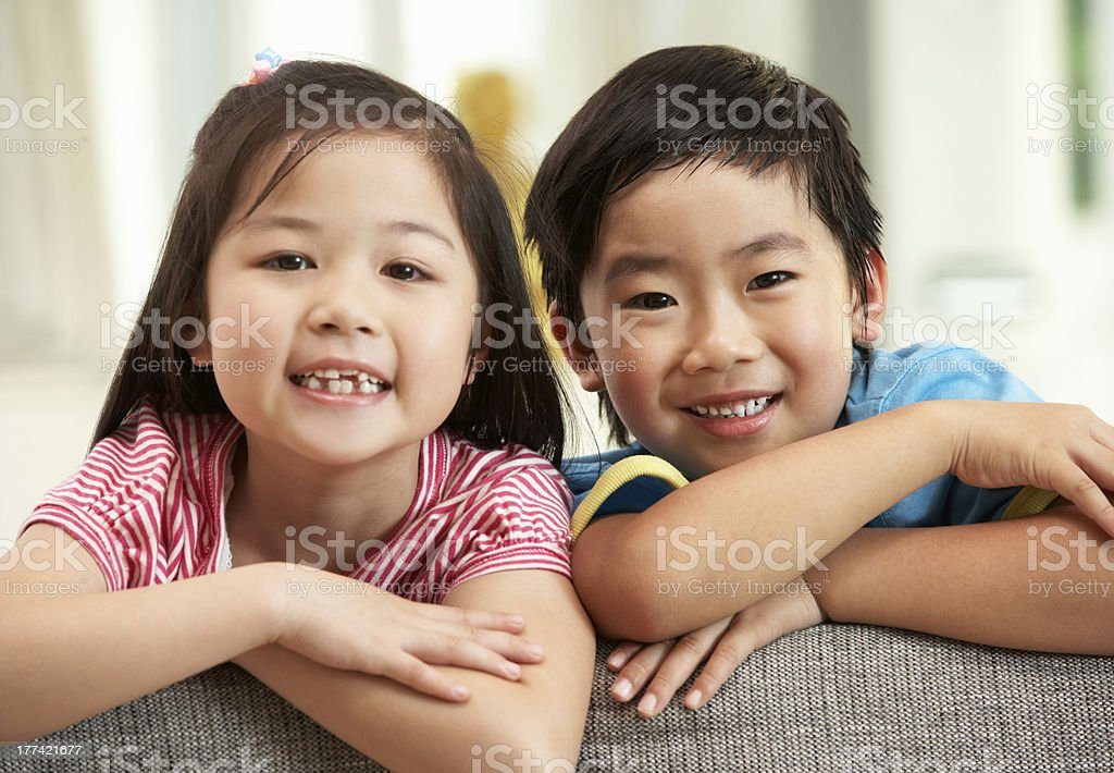 Two Chinese Children Relaxing On Sofa At Home stock photo