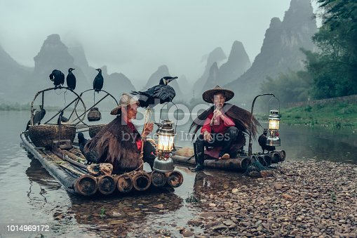 Two chinese cormorant fishermen taking a break for smoking on bamboo raft on lee river