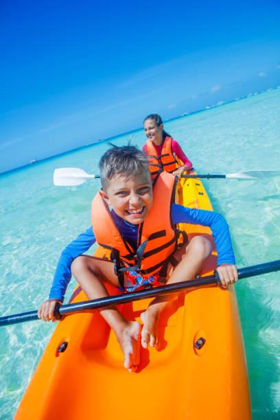 Two chirdren kayaking at tropical sea on yellow kayak stock photo