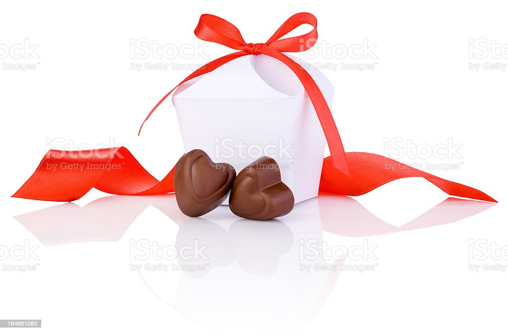 Two chocolate candies in heart shape, white box, red ribbon royalty-free stock photo