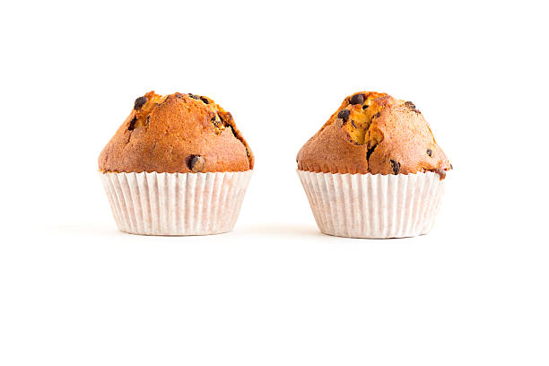 Two chocolate chip muffins isolated on white