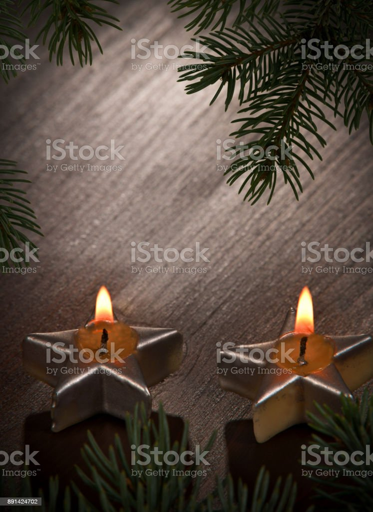 Two Christmas Candles with Twig on the Desk stock photo