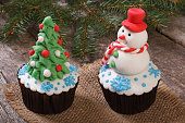 Two Christmas cupcake: Christmas tree and snowman on the table