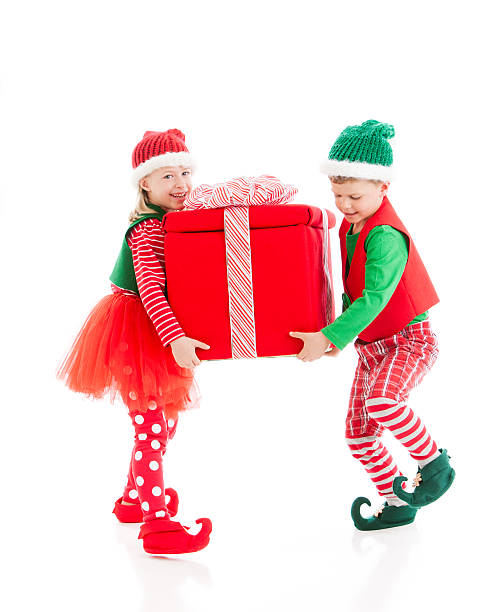 two christmas elves carry a big heavy wrapped present - pixie dust bildbanksfoton och bilder