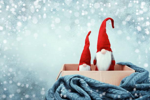 dos gnomos navideños en caja abierta, manta de punto - accesorio de cabeza fotografías e imágenes de stock