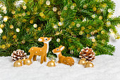 istock Two Christmas reindeer and golden balls in snow with pine tree and bokeh as background. Festive holiday greeting card. Merry Christmas and New Year 1288618765