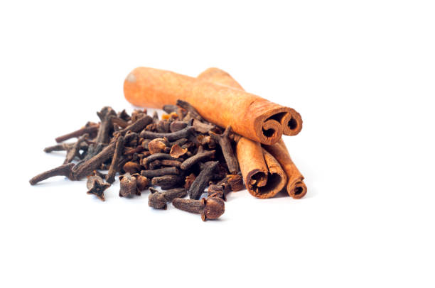 Two cinnamon sticks and a pile of dried cloves cloves on a white background Two cinnamon sticks and a pile of dried cloves cloves on a white background clove spice stock pictures, royalty-free photos & images