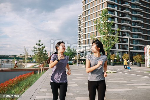 Two young women jogging together down the city promenade.
