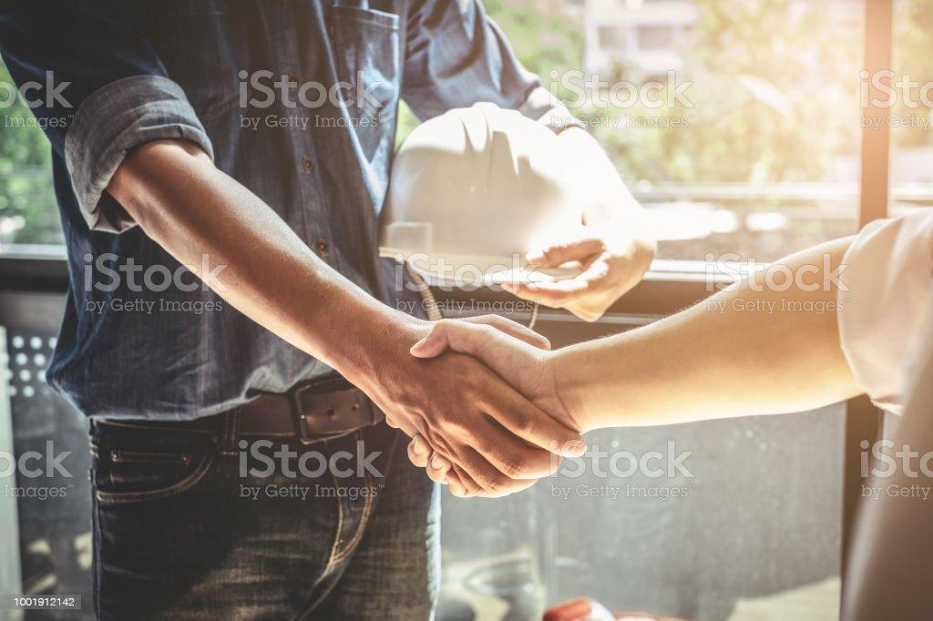 Zwei Bauingenieur oder Architekt Holding Helm und Handshake nach Mega-Projekt durchgeführt. Ingenieur, ein Bau-Projekt-Konzept zu skizzieren. – Foto