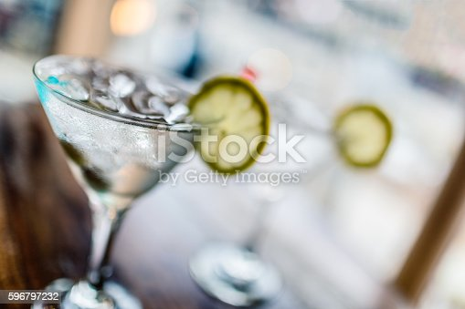 Two glasses of classic martinis with ice on a hot Summer day. Selective focus on the foreground glass.