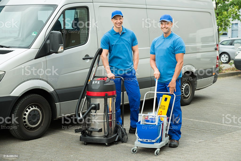 Two Cleaners Standing With Cleaning Equipments stock photo