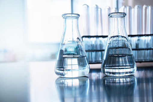 istock two clear flask with water in front of test tube in education chemistry science laboratory background 1132055911