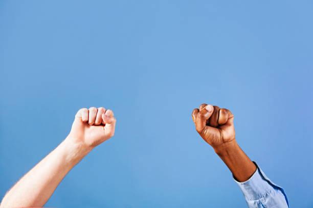兩個緊握的拳頭對藍色背景 - black power 個照片及圖片檔