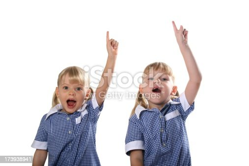 istock Two Clever School Girls with hands up on white background 173938941