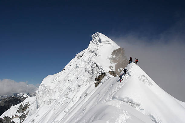 Two climbers almost at the top of a snowy mountain top stock photo