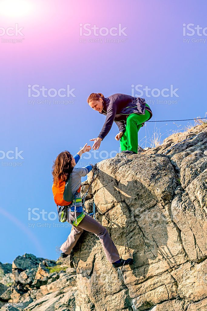 Two climbers assysting each other to get the summit stock photo