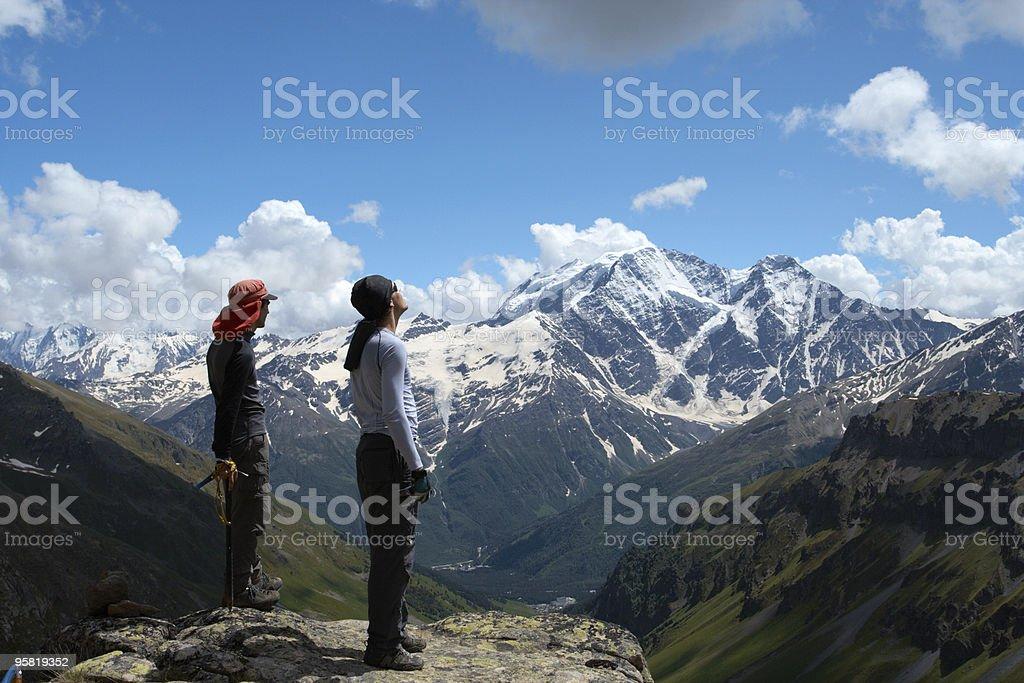 two climbers looking at the mountains stock photo