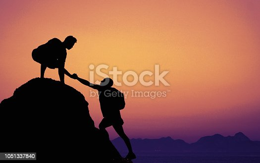 Two climbers on mountain peak on sunset as symbol for teamwork and assitance