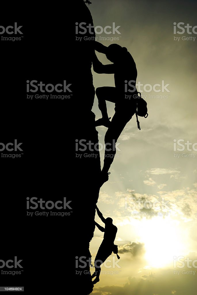 Two climbers on sheer rock face silhouetted against sky royalty-free stock photo