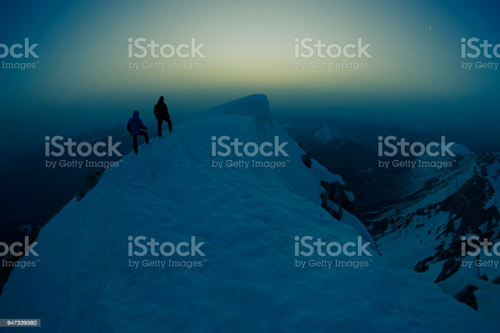 Two climbers on top of a mountain at night stock photo