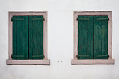 Two closed old windows with wooden shutters